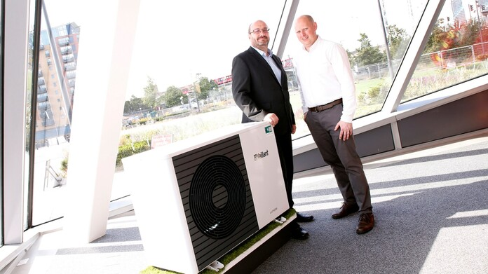 Two men standing next to an aroTHERM heat pump