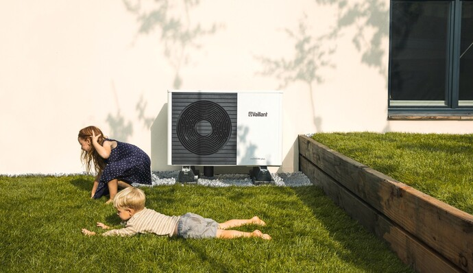 Vaillant's aroTHERM plus in a garden with children playing in front of it