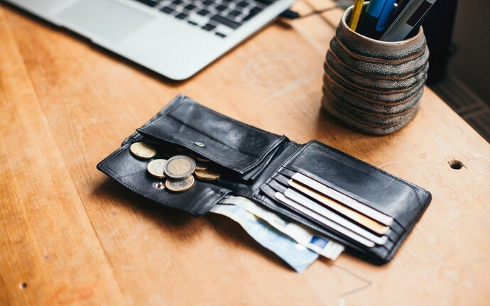 An open black wallet on a desk with money falling out of it