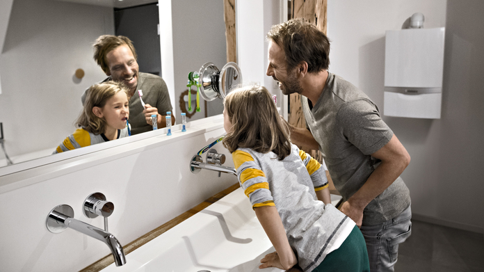 New boiler - father and son brushing their teeth in the bathroom with heating system in the background