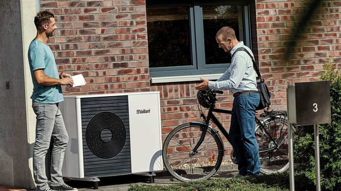 2 people talking in front of an aroTHERM split air source heat pump