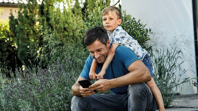 A father carries his son piggyback and smiles on his smartphone. Both are smiling.