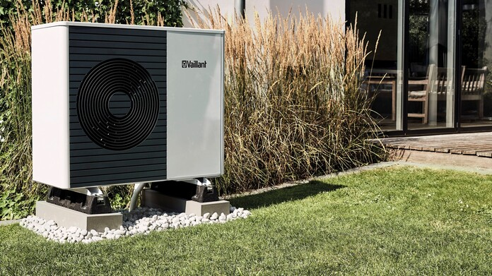Outdoor unit of a heat pump in front of a modernised house